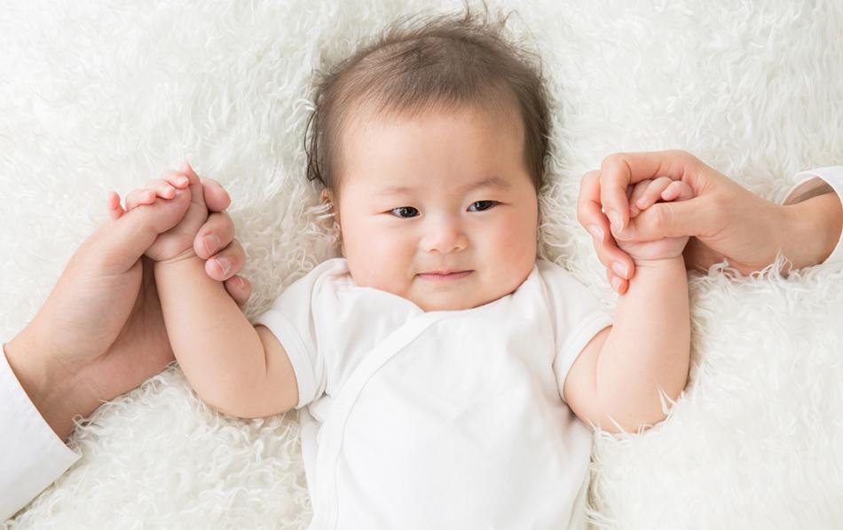 両手を握られる赤ちゃん