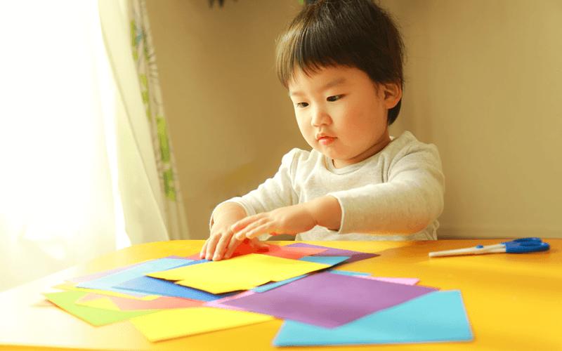 折り紙で遊ぶ子供